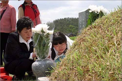 모녀가 무덤앞에서 눈물을 흘리고 있다.