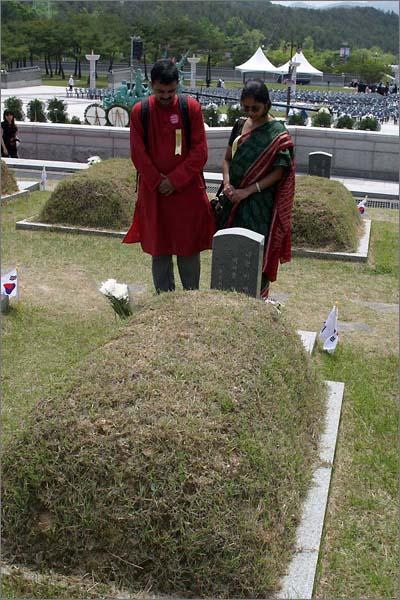 외국인들이 묘지 앞에서 묵념을 올리고 있다.