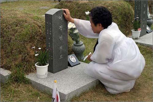 한 할머니가 묘비를 쓰다듬고 있다.
