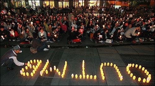 """미국산 쇠고기 수입 전면 개방을 반대하는 시민이 21일 저녁 서울 청계광장에서 열린 촛불문화제에서 정부의 미국산 쇠고기 수입 정책 철회를 촉구하며 촛불로 """"OUT MB""""라고 글자를 만들고 있다."""