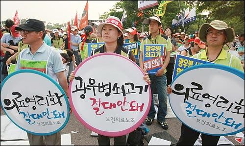 보건의료노동조합원들이 24일 오후 서울 여의도 여의도 문화마당에서 열린 민주노총 총력투쟁 결의대회에서 정부가 공공부문을 민영화하려는 계획을 철회를 요구하며 피켓을 들어보이고 있다.