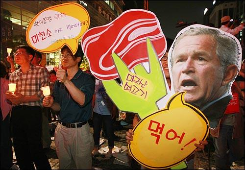 미국산 쇠고기 수입 전면 개방을 반대하는 학생과 시민들이 지난 24일 저녁 서울 청계광장에서 열린 광우병위험 미국산쇠고기 수입반대 제17차 촛불문화제에서 정부의 미국산 쇠고기 수입 정책 철회를 촉구하며 피켓을 들어보이고 있다.