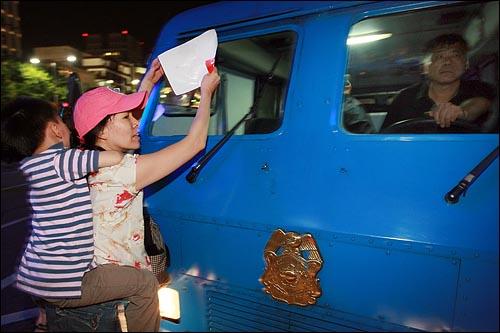 어린 아이를 등에 업은 어머니가 24일 저녁 서울 세종로사거리 앞에서 청와대로 행진하던 도중 해산을 요구하는 경찰 방송차 창문을 두드리며 정부의 미국산 쇠고기 수입 정책 철회를 촉구하고 있다.