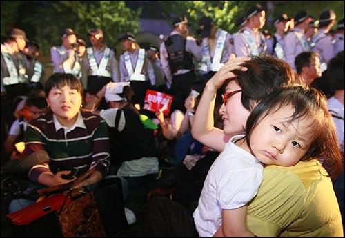 미국산 쇠고기 수입에 반대하는 촛불문화제에 참석했던 시민이 24일 밤 세종로 사거리에서 촛불문화제 행사를 마친뒤 청와대로 행진하려다가 경찰들에게 막히자 아이를 안고 도로에 앉아 시위를 하고 있다.