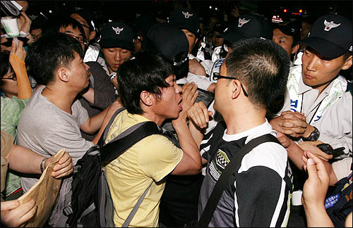 미국산 쇠고기 수입에 반대하는 촛불문화제에 참석했던 학생과 시민들이 24일 밤 행사를 마친 뒤 청와대로 행진하려하자 경찰이 이들을 막고 나서 몸싸움을 벌이고 있다.