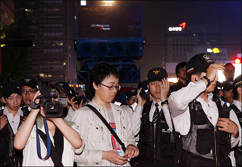 미국산 쇠고기 수입에 반대하는 촛불문화제에 참석했던 학생과 시민들이 24일 밤 행사를 마친 뒤 청와대로 행진하려 하자 경찰이 살수차를 동원해 '자진해산'을 경고하며 이들을 가로막고 서 있다.