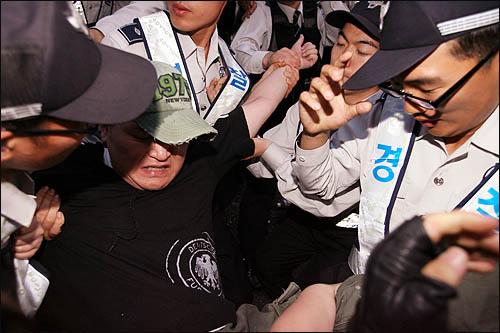 25일 새벽 종로 거리를 점거한 채 미국산 쇠고기 수입 반대 집회를 열고 있던 시민들을 경찰이 강제 연행하고 있다.