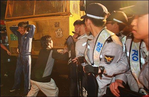 미국산 쇠고기 수입을 반대하는 시민이 25일 새벽 4시 20분쯤 서울 종로 거리에서 경찰 살수차가 쏘는 물대포를 몸으로 막고 있다.