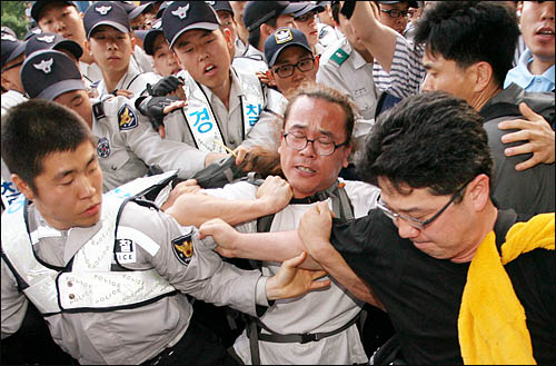 25일 새벽 종로 거리를 점거한 채 미국산 쇠고기 수입 반대 집회를 열고 있던 시민들을 경찰이 강제 연행하기 위해 끌어내고 있다.