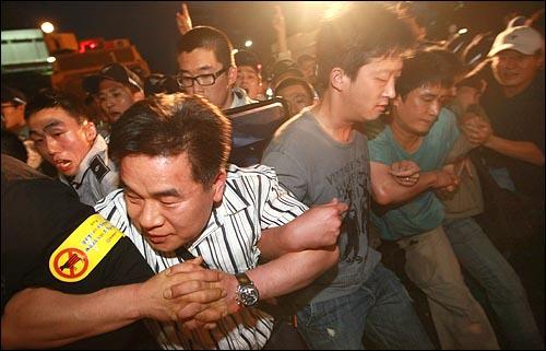 25일 새벽 4시 50분쯤 종로 거리를 점거한 채 미국산 쇠고기 수입 반대 집회를 열고 있던 시민들이 경찰들의 강제 연행에 맞서 스크럼을 짜고 경찰과 대치하고 있다