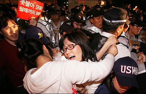25일 새벽 종로 거리를 점거한 채 미국산 쇠고기 수입 반대 집회를 열고 있던 시민들을 경찰이 연행하려하자 참가자들이 필사적으로 버티고 있다.