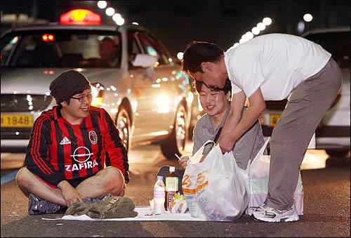 미국산 쇠고기 수입에 반대하는 학생과 시민들이 25일 새벽 종로 거리를 점거한 채 밤샘 농성을 벌이고 있다. 한 집회 참가자가 간식을 나눠주고 있다.