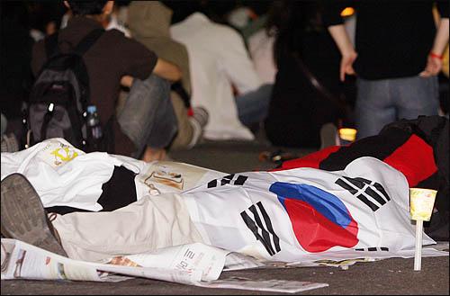 미국산 쇠고기 수입에 반대하는 학생과 시민들이 25일 새벽 종로 거리를 점거한 채 밤샘 농성을 벌이고 있다. 새벽 4시가 가까워오자 아예 바닥에 신문을 깔고 눈을 붙이는 이들도 눈에 띈다.