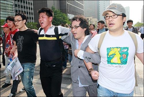 경찰들과 대치 상황을 마친 학생과 시민들이 25일 오전 서울 청계광장에 모여 정부의 미국산 쇠고기 수입 정책 철회를 촉구하며 구호를 외치고 있다.