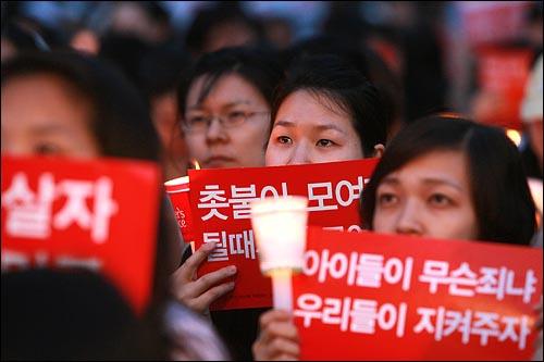 광우병위험 미국산쇠고기 수입반대 촛불문화제가 25일 저녁 서울 청계광장에서 열리는 가운데 한 여성이 참가자들의 자유발언을 들으며 눈물을 글썽이고 있다.