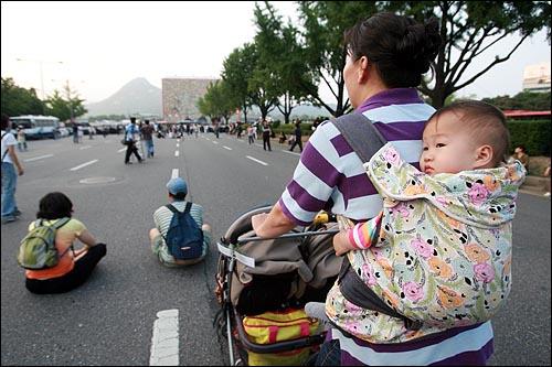 25일 오후 광우병위험 미국산쇠고기 수입반대 밤샘시위를 강제진압한 것에 항의하는 시민들이 청와대로 행진을 벌이는 가운데 아이를 업고 유모차에 태운 한 여성이 세종로 거리에서 청와대를 바라보고 있다.