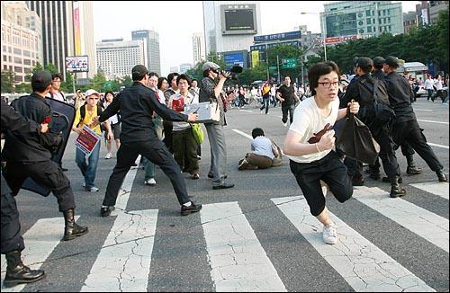 25일 오후 서울 청계광장에서 광우병위험 미국산쇠고기 수입반대 밤샘농성 강제진압에 항의하던 시민들 중 일부가 경찰저지선을 뚫고 청와대를 향해 달리고 있다.