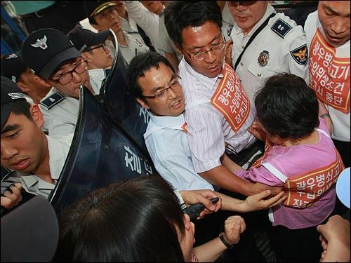 미국산 쇠고기 고시 반대와 재협상을 촉구하는 삼보일배에 동참한 박정숙 민주노동당 18대 당선자와 시민단체 회원들이 26일 오후 서울 광화문 정부청사후문에서 경찰의 제지에 막혀 몸싸움을 하고 있다.