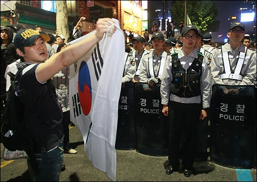 26일 밤 서울 청계광장에서 열린 광우병위험 미국산쇠고기 수입반대 촛불문화제에 참석했던 시민이 촛불집회를 마친 뒤 종로거리로 나와 '이명박 탄핵' '고시 반대' '협상 무효'을 외치며 태극기를 들어보이고 있다.