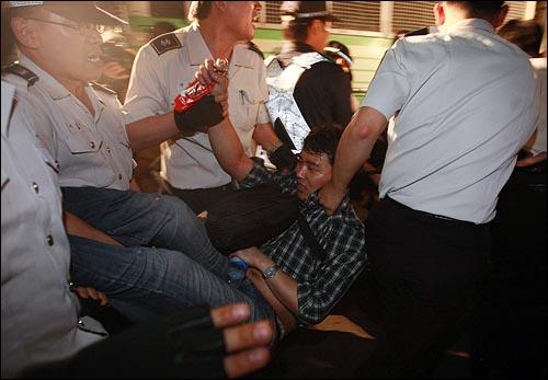 27일 새벽 종로 거리를 점거한 채 미국산 쇠고기 수입 반대 집회를 열고 있던 시민들을 경찰들이 강제 연행하고 있다.