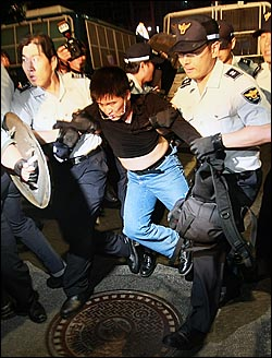 27일 새벽 종로 거리를 점거한 채 미국산 쇠고기 수입 반대 집회를 열고 있던 시민들이 경찰들에게 강제 연행되고 있다.