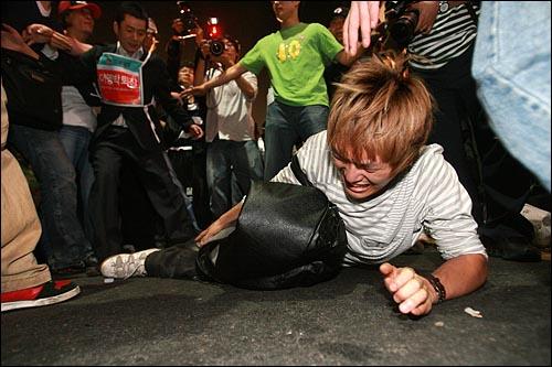 27일 새벽 서울 종로 종각역 부근에서 광우병위험 미국산쇠고기 수입반대 시위를 벌이던 시민들이 경찰의 토끼몰이식 진압에 밀려 쓰러지면서 여러명이 부상을 당했다. 다리를 심하게 다친 한 시민이 일어서지 못한 채 고통스러워 하고 있다.