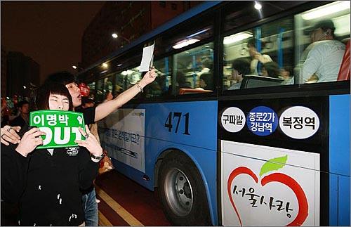 미국산 쇠고기 수입 전면 개방을 반대하는 학생과 시민들이 27일 저녁 서울 청계광장에서 열린 광우병위험 미국산쇠고기 수입반대 촛불문화제를 마친뒤 명동으로 행진하며 버스를  탄 시민들에게 손피켓을 들어보이고 있다.