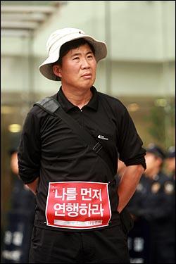 광우병위험 미국산쇠고기 수입반대 21차 촛불문화제가 열리는 28일 저녁 서울 청계광장에서 한 시민이 '나를 먼저 연행하라'는 글이 적힌 천에 자신의 이름을 적어서 옷에 붙이고 있다.