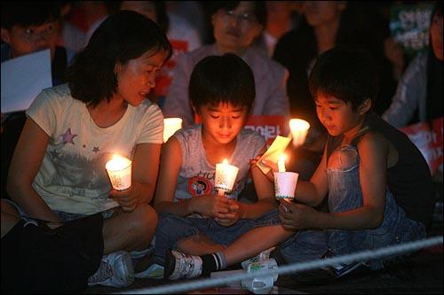 28일 저녁 서울 청계광장에서 열리는 광우병위험 미국산쇠고기 수입반대 21차 촛불문화제에서 가족들이 촛불을 들고 있다.