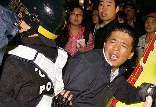 광우병 위험으로부터 안전하지 않은 미국산 쇠고기 수입에 반대하는 시민과 학생들이 28일 밤 서울 무교동 일대에서 인도까지 가로막고 있는 경찰에게 항의하고 있다.