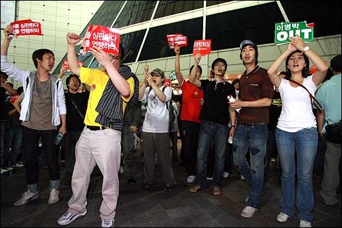 29일 새벽 서울 동대문 두산타워앞에 전날 저녁 청계광장에서 열린 광우병위험 미국산쇠고기 수입반대 21차 촛불문화제에 참가했던 시민들이 모여 '고시 반대' '이명박 퇴진' 구호를 외치고 있다.