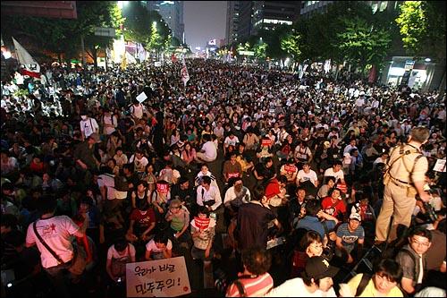 한미 쇠고기 협상에 대한 장관 고시가 발표된 29일 저녁 서울시청앞 광장에서 열린 촛불문화제에 참석한 수만명의 시민들이 거리행진을 벌인 뒤 광화문우체국앞에서 경찰버스로 만든 바리케이트에 막히자 연좌시위를 벌이고 있다.