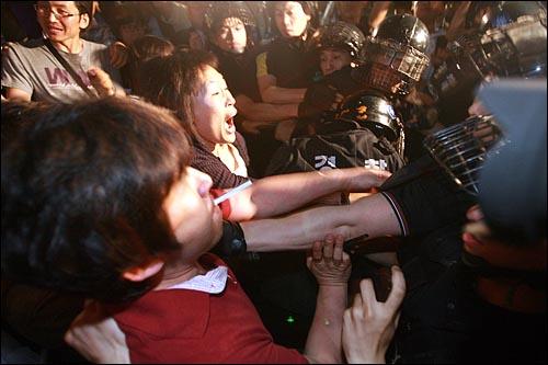 한미 쇠고기 협상 장관 고시 무효를 주장하며 밤샘농성을 벌이던 시민, 학생들이 30일 새벽 서울 세종로 네거리 광화문우체국앞 도로에서 인도로 밀어내는 경찰과 몸싸움을 벌이고 있다.