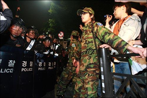 한미 쇠고기 협상 장관 고시 무효를 주장하며 30일 새벽까지 서울 세종로 네거리 도로에거 농성을 벌이던 시민, 학생들을 경찰이 강제해산시키자 예비군복을 입은 시민들이 경찰 앞을 가로막고 있다.