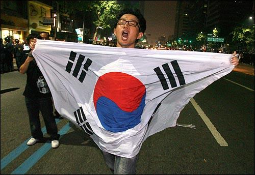 한미 쇠고기 협상 장관 고시 무효를 주장하며 30일 새벽까지 서울 세종로 네거리 도로에거 밤샘농성을 벌이던 시민, 학생들을 경찰이 강제해산시키자 한 참가자가 태극기를 펼쳐들고 도로에서 항의시위를 벌이고 있다,