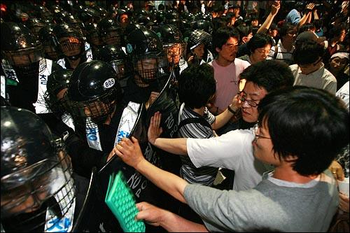 한미 쇠고기 협상 장관 고시 무효를 주장하며 30일 새벽까지 서울 세종로 네거리 도로에거 밤샘농성을 벌이던 시민, 학생들을 경찰이 강제해산시키기 위해 진입해 들어가고 있다.