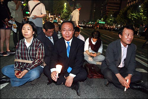한미 쇠고기 협상 장관 고시 무효를 주장하며 30일 새벽까지 서울 세종로 네거리 도로에서 밤샘농성을 벌이던 시민, 학생들을 경찰이 강제해산시키는 가운데 진보신당 노회찬 대표와 조승수 전 의원이 당원들과 함께 도로에서 연좌시위를 벌이고 있다.