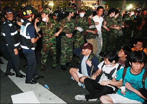 한미 쇠고기 협상 장관 고시 무효화를 주장하며 30일 새벽까지 서울 세종로 네거리 도로에서 연좌농성을 벌이던 시민과 학생들을 경찰들이 강제해산시킬 준비를 하자 예비군복을 입은 시민들이 경찰 앞을 가로막고 있다.