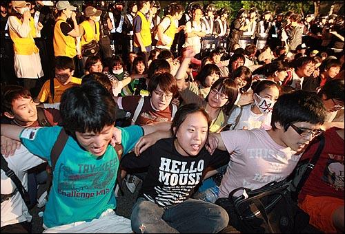 한미 쇠고기 협상 장관 고시 무효화를 주장하며 30일 새벽까지 서울 세종로 네거리 도로에서 연좌농성을 벌이던 시민과 학생들이 경찰들에게 둘러싸이자 어깨동무를 하고 '임을 위한 행진곡'을 부르고 있다.