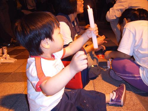 촛불을 들고 주먹을 불끈 쥔 세살짜리 아이