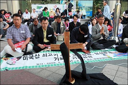기독교연합회단체 회원들이 30일 오후 서울 광화문 네거리 동화면세점 앞에서 정부의 미국산쇠고기 고시 철회와 재협상을 촉구하는 기자회견을 마친뒤 철야 촛불기도회를 하고 있다.