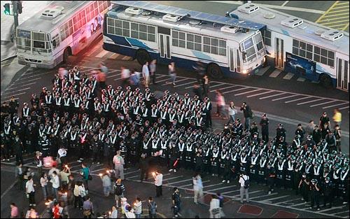 미국산 쇠고기 수입 전면 개방을 반대하는 학생과 시민들이 30일 저녁 서울 시청광장에서 열린 광우병위험 미국산 쇠고기 수입반대 제23차 촛불문화제를 마친뒤 종로로 행진하다가 경찰 병력과 버스로 진입로가 차단되어 있다.