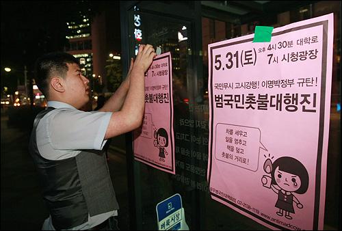 촛불집회 자원봉사자가  30일 저녁 서울 시청광장에서 열린 광우병위험 미국산 쇠고기 수입반대 제23차 촛불문화제를 마친뒤 행진을 하며 31일 '시청광장 범국민촛불대행진' 행사를 알리는 포스터를 붙이고 있다.