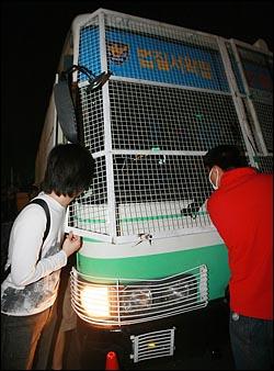 30일 밤 서울 시청광장에서 열린 촛불문화제를 마친뒤 시가행진하는 시민들과 경찰이 대치를 벌이던 중 덕수궁 앞에서 전경버스에 시민이 치이는 사고가 나자 시민들이 가해 전경버스 안을 보고 있다.