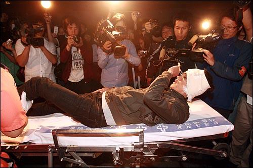 31일 새벽 서울시청앞 광장에서 광우병위험 미국산쇠고기 수입반대 시위대를 경찰이 해산시키는 과정에서 경찰에 밀려 쓰러딘 뒤 귀를 다친 한 시민이 119구급대에 의해 병원으로 옮겨지고 있다.