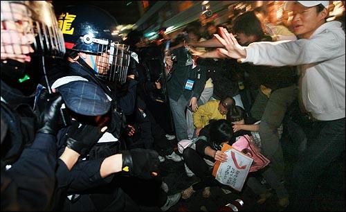 31일 새벽 서울 시청광장에서 열린 광우병위험 미국산 쇠고기 수입반대 촛불문화제를 마친 뒤 덕수궁 앞에서 전경버스가 시민을 친 사고가 벌어져 학생과 시민들이 가해 운전자의 사과를 요구하자 경찰들이 강제로 인도로 밀어 올리고 있다.