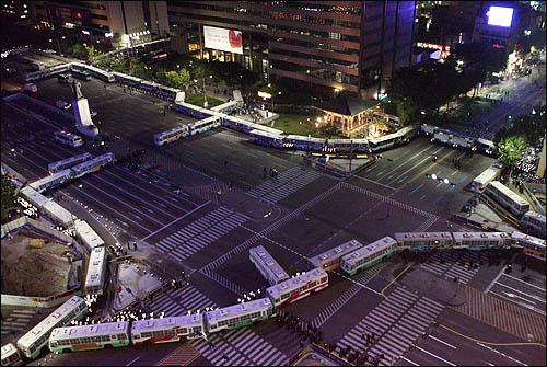 31일 밤 서울 시청 앞 광장에서 열린 미국산 쇠고기 수입반대 촛불문화제에 참가한 시민들이 거리행진을 시작한 가운데 광화문 사거리는 전경차와 경찰 병력으로 원천 봉쇄돼있다.