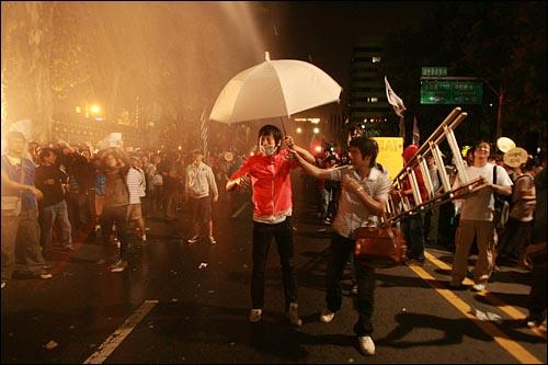 1일 새벽 서울 효자동 청와대 입구에서 경찰이 광우병위험 미국산쇠고기 수입반대 및 재협상을 요구하며 '이명박 나와라'를 외치는 시민,학생들에게 살수차(물대포)로 물을 뿌리고 있다.