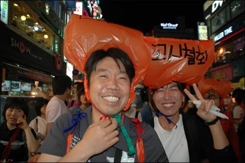 촛불문화제에 참석한 시민들이 쓰레기 봉투에 구호를 적어 머리에 모자처럼 쓰고 있다.