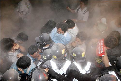 미국산 쇠고기 수입을 반대하는 시민들이 31일 밤 서울 삼청동에서 청와대 방향으로 진격하자 경찰이 소화분말을 뿌리고 있다.